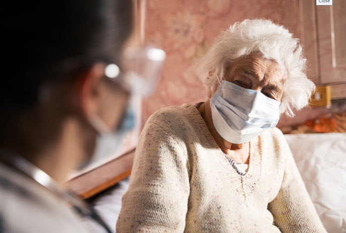 nurse talking to masked elderly woman on couch